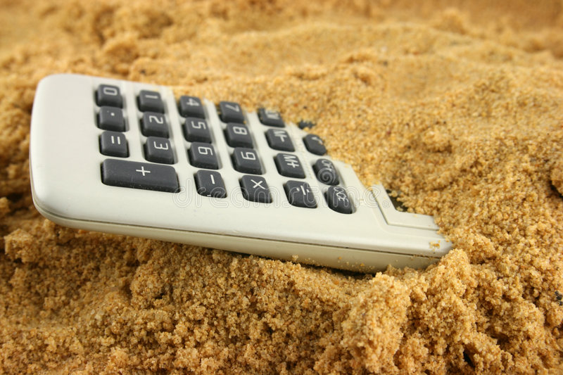 Numbers in the Sand. Calculator buried in the sand with numbers showing royalty free stock images