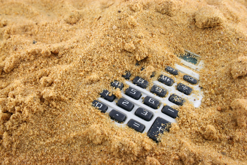 Numbers in the Sand. Calculator buried in the sand with numbers showing royalty free stock photography