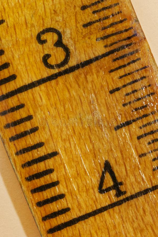 Yellow ruler with numbers. Numbers three and four on a yellow wooden ruler , black lines along the edges ,the ruler is worn out stock images