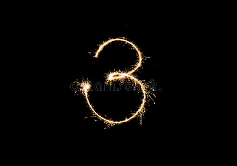 Numbers 3 or three Sparkler firework light isolated on black background stock images
