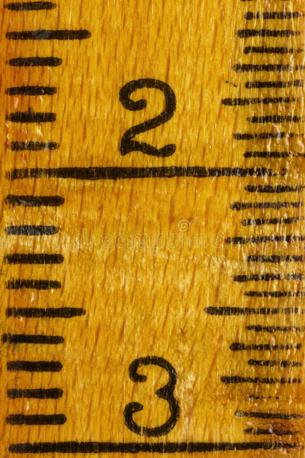 Yellow wooden ruler. Numbers two and three on a yellow wooden ruler , black lines along the edges ,the ruler is worn out royalty free stock images
