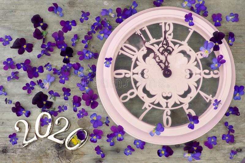 2020 numbers on a wooden background next to purple pansies flowers and a pink clock showing five minutes to midnight stock photo