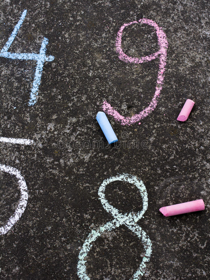 Numbers written in colorful chalk on the asphalt. Selective focus stock photo