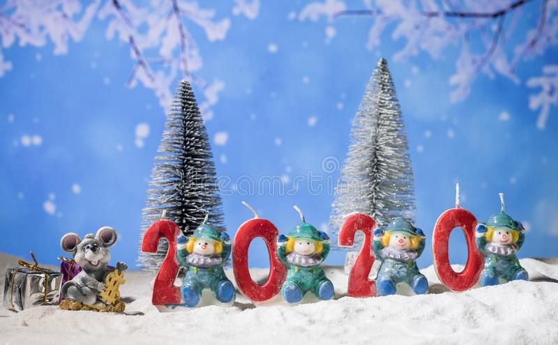 The numbers for the year 2020 stand in the snow with a pine branch decoration and a little imp sit on the left site with a. The numbers for the year 2020 stand royalty free stock image