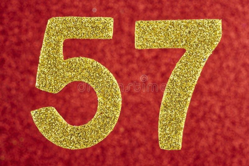 Numere cinquenta e sete cores do ouro sobre um fundo vermelho anniversary imagens de stock