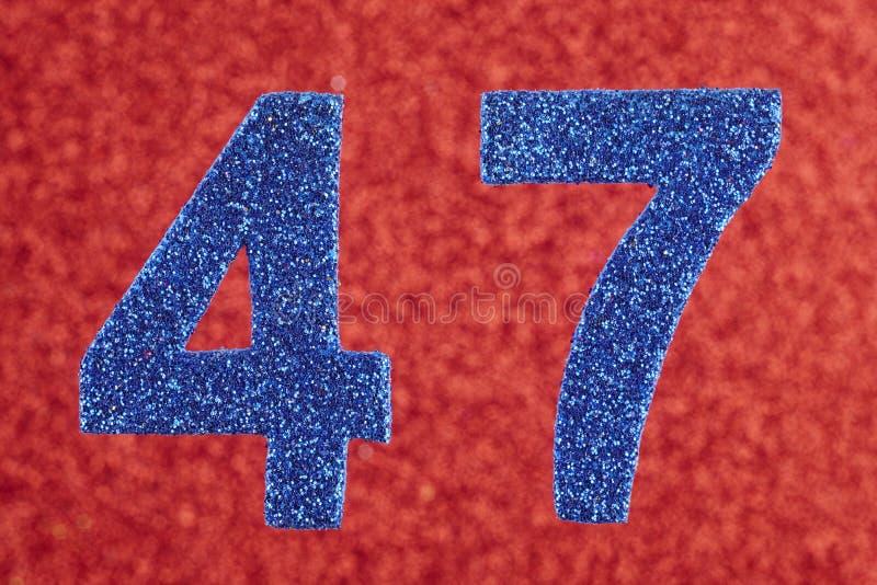 Numere quarenta e sete cores do azul sobre um fundo vermelho anniversary fotos de stock