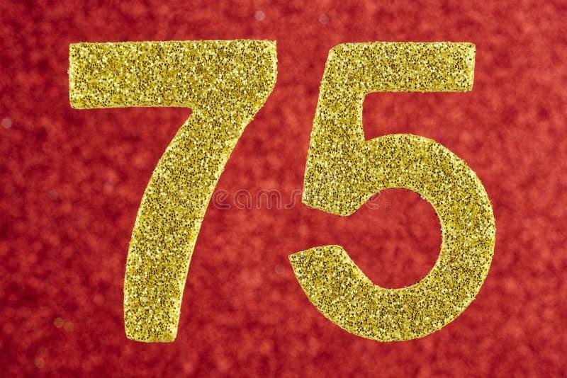 Numere setenta y cinco colores de oro sobre un fondo rojo Annivers foto de archivo libre de regalías