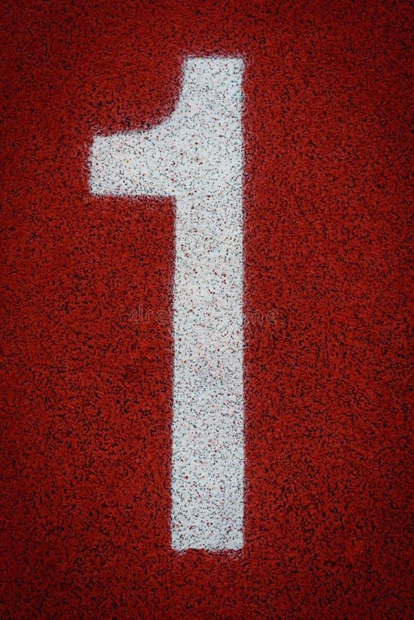 Numere um no começo de uma pista de atletismo foto de stock