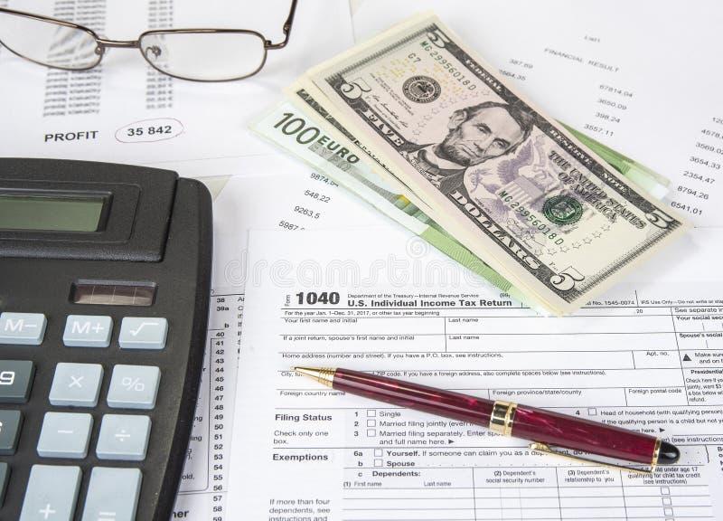 Numeri calcolatori per dichiarazione dei redditi con la penna, i vetri ed il calcolatore immagini stock