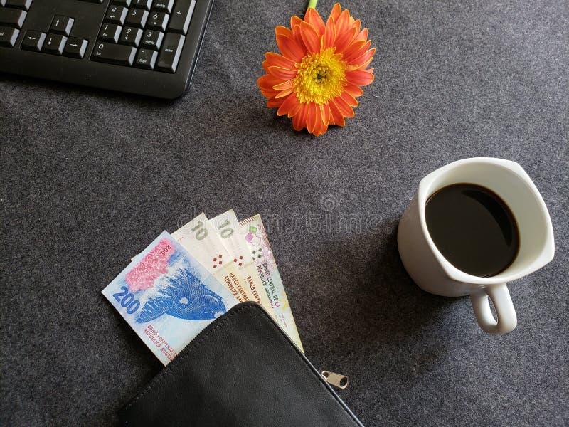 numeriek toetsenbord van een computer, een gerberabloem, een koffiekop en een zwarte portefeuille met Argentijnse bankbiljetten o stock afbeelding