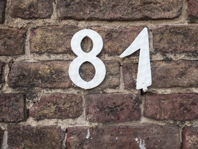 Numero civico bianco 81 su un vecchio muro di mattoni immagini stock libere da diritti