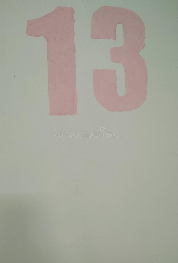 numero 13 disegnato attraverso la pittura di rosa dello stampino su un primo piano blu-chiaro del primo piano del fondo illustrazione vettoriale