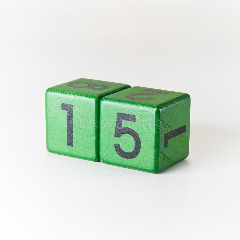 Numero quindici scritto su un cubo verde di legno su fondo bianco fotografia stock