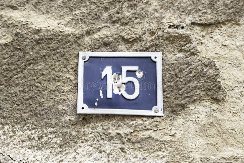 Numero quindici su una parete di una casa fotografie stock
