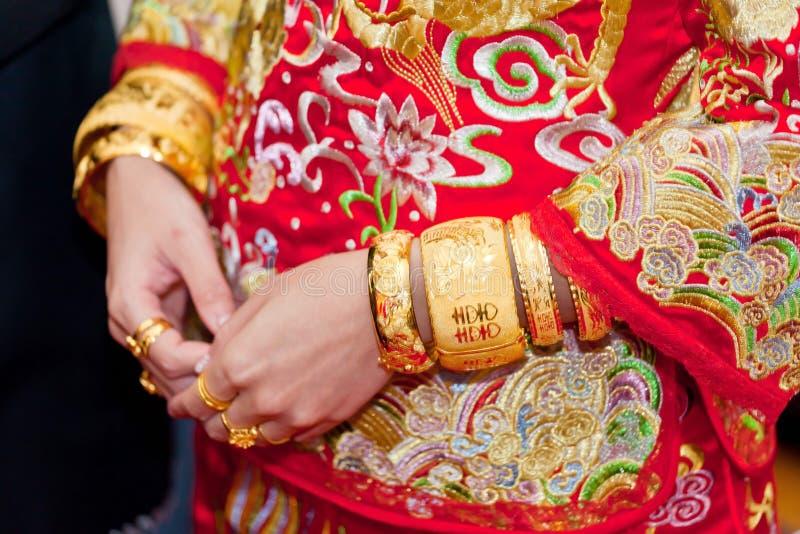 Numerous golden wedding bangles on Chinese bride royalty free stock photo