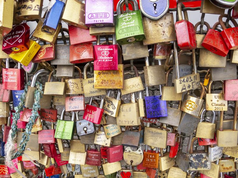 Numerous love padlocks on the fence between the footpath and the railway lines of Hohenzollern Bridge in Cologne, Germany, texture stock photography