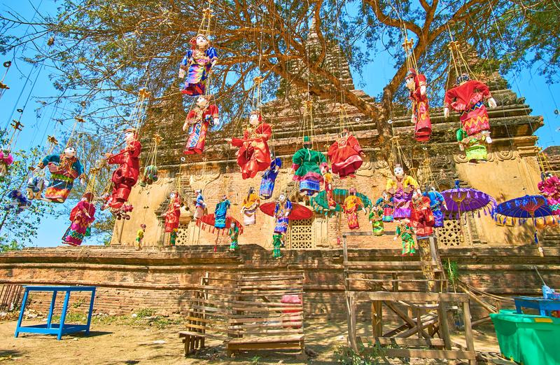 Burmese marionettes in the courtyard of the temple, Bagan, Myanmar. Numerous marionettes in burmese style hanged in the courtyard of medieval shrine in Bagan stock images