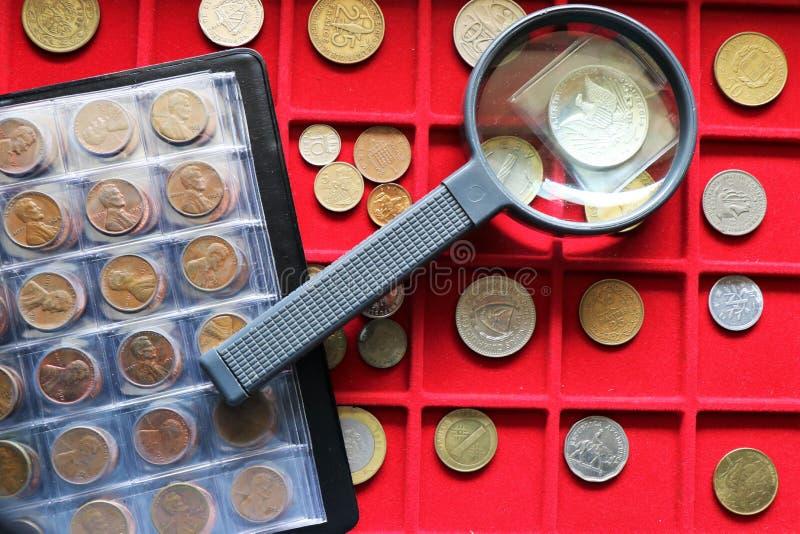 Numismatico, raccolta di monete del mondo su un vassoio rosso immagine stock libera da diritti