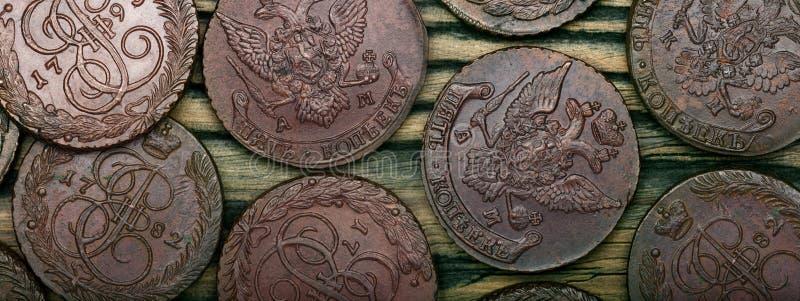 numismatics Las monedas cobrables viejas hicieron del cobre en una tabla de madera vieja imágenes de archivo libres de regalías