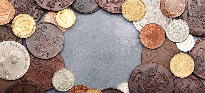 numismatics Monedas cobrables viejas hechas de la plata, del oro y del cobre en una tabla Visi?n superior foto de archivo