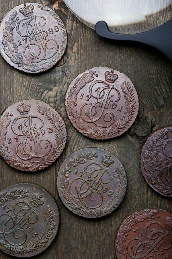 numismatics Oude inbare die muntstukken van koper op een oude houten lijst worden gemaakt stock fotografie