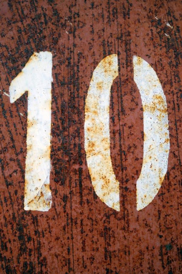 Nummer 10 i stencil på den grungy orange färgmetallväggen royaltyfria bilder