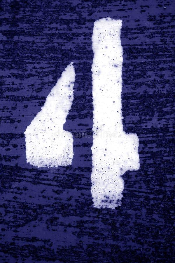 Nummer 4 i stencil p? den grungy metallv?ggen i bl? signal arkivfoto
