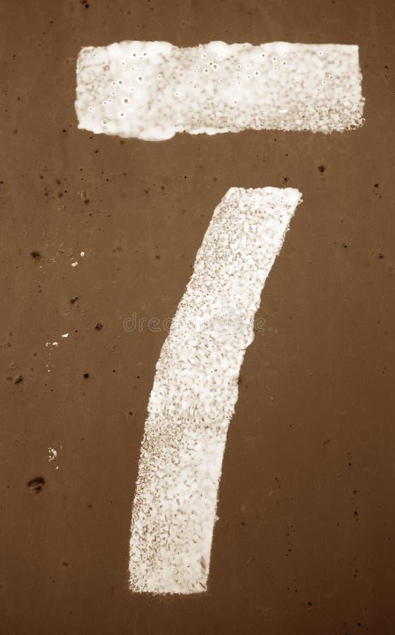Nummer 7 i stencil p? metallv?ggen i brun signal arkivbild