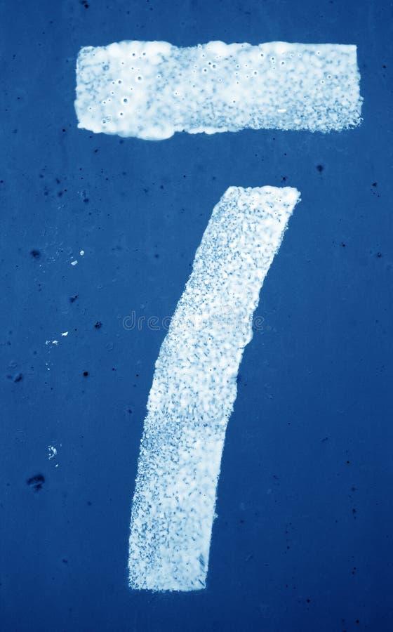 Nummer 7 i stencil p? metallv?ggen i marinbl? signal royaltyfri foto