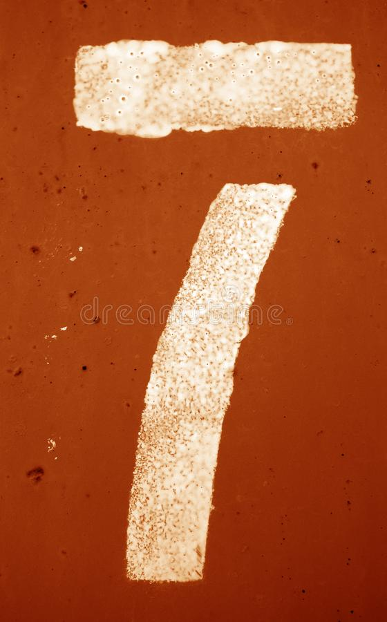 Nummer 7 i stencil p? metallv?ggen i orange signal royaltyfria foton