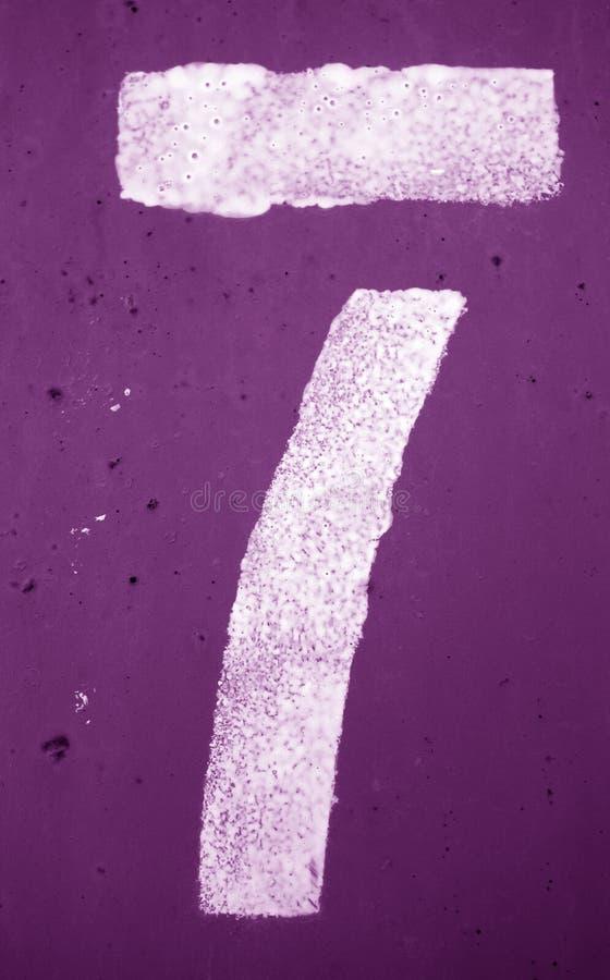 Nummer 7 i stencil p? metallv?ggen i purpurf?rgad signal royaltyfri fotografi