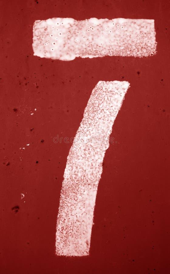 Nummer 7 i stencil p? metallv?ggen i r?d signal royaltyfria foton