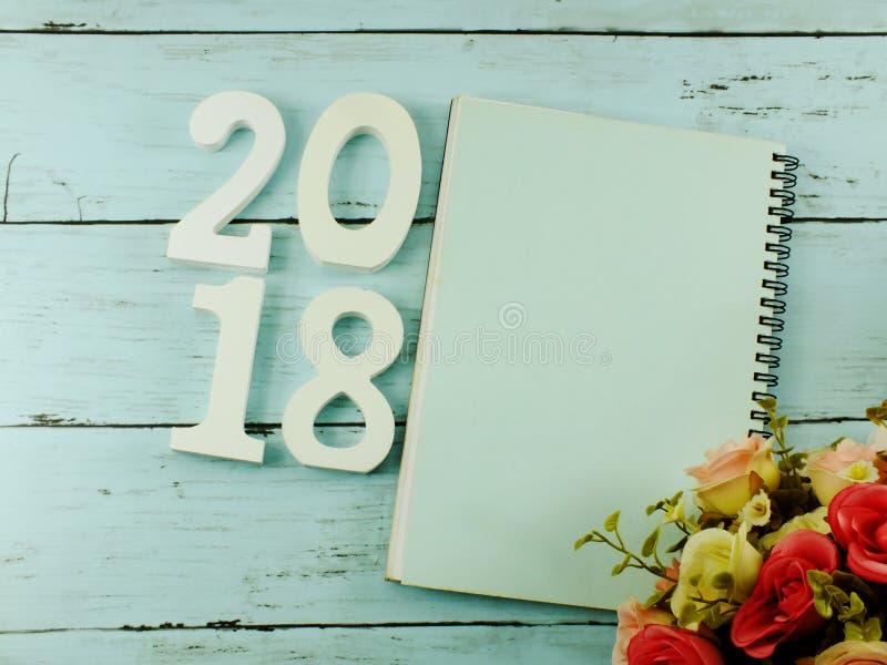 Nummerieren Sie hölzernes neues Jahr auf Notizbuch des leeren Papiers auf hölzernem Hintergrund lizenzfreie stockfotografie