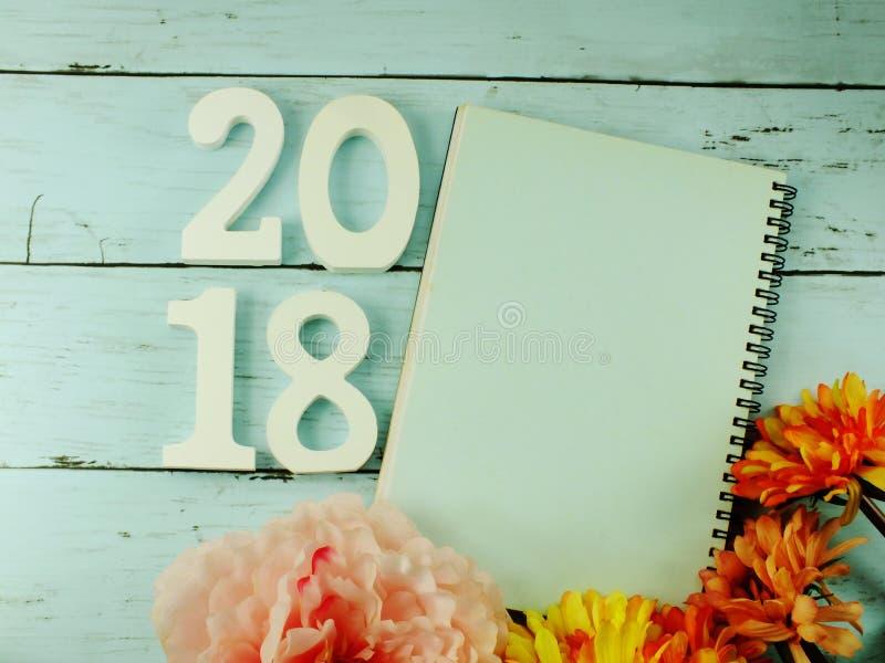 Nummerieren Sie hölzernes neues Jahr auf Notizbuch des leeren Papiers auf hölzernem Hintergrund stockfoto