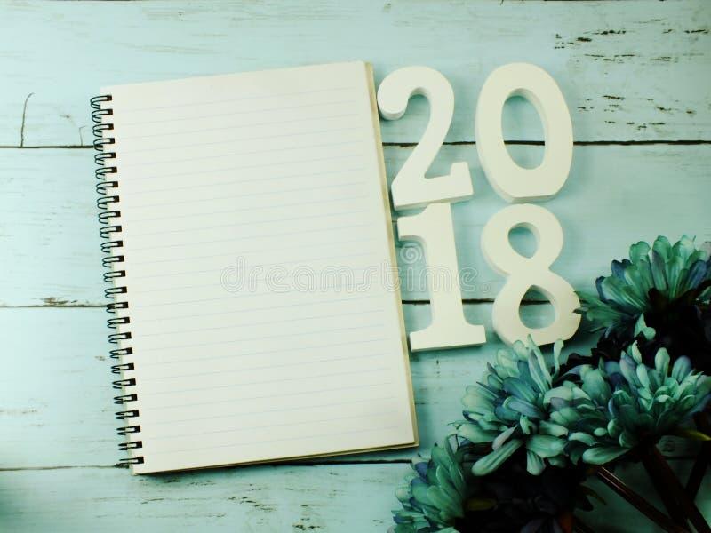 Nummerieren Sie hölzernes neues Jahr auf Notizbuch des leeren Papiers auf hölzernem Hintergrund lizenzfreies stockbild