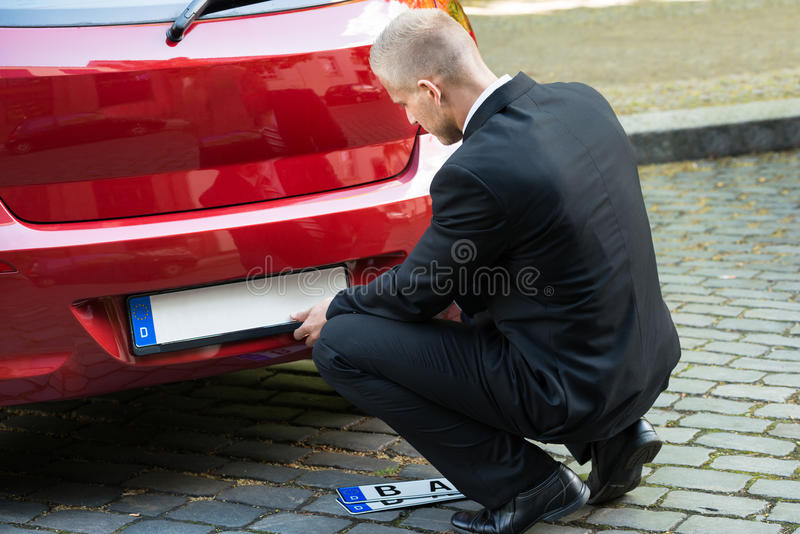 Nummerplaat van de mensen de veranderende auto stock afbeelding