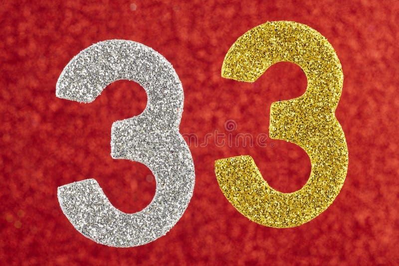 Numrera trettiotre gula silverfärg över en röd bakgrund fotografering för bildbyråer