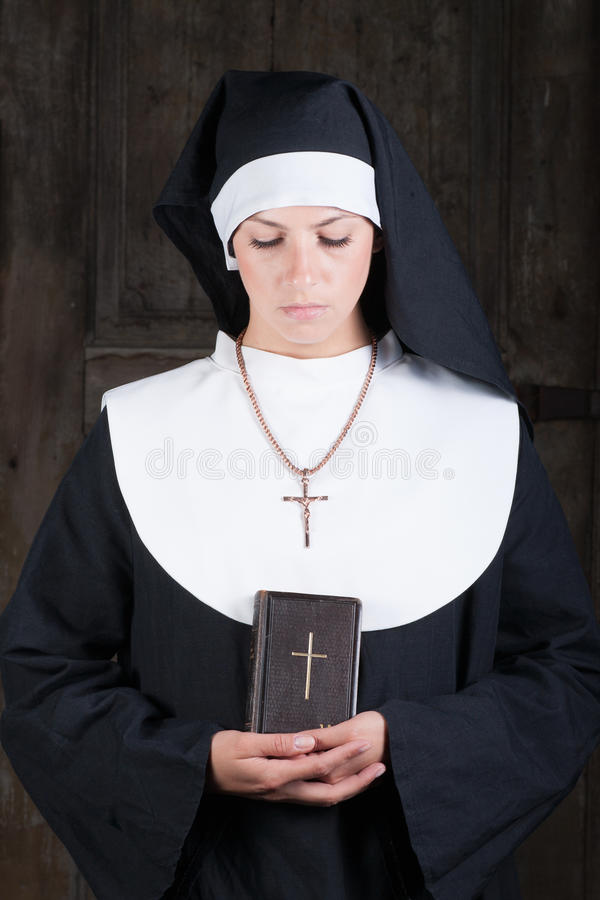 Nun with Bible. Looking down stock image
