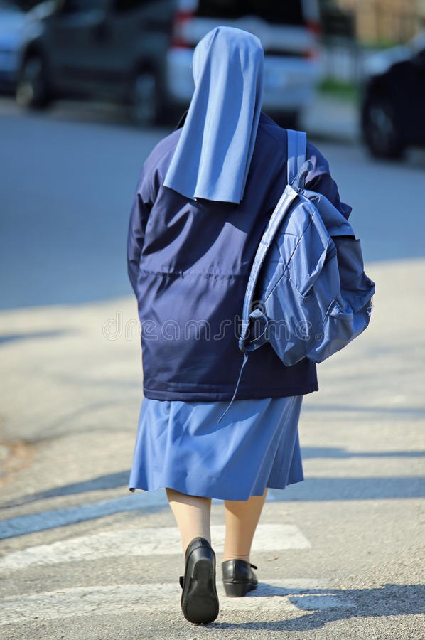 nun with blue dress and veil with a backpack stock image