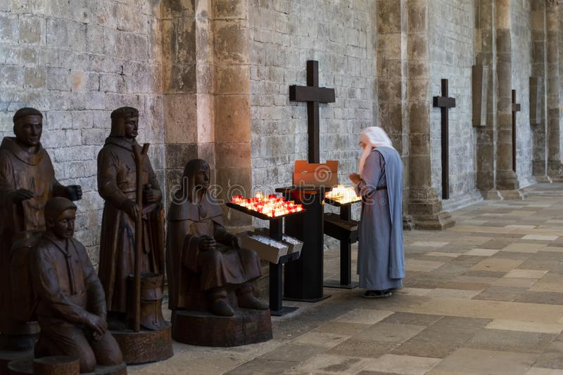 Nun in Church Vezelay Yonne. Vezelay, France - July 29, 2018: Church Interior with nun rearranging the candles of the romanesque abbey and church of Vezelay in royalty free stock images
