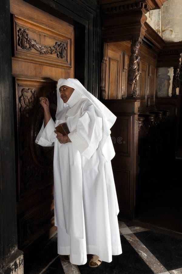 Nun knocking on door. Nun knocking on the vicar's door in a medieval church stock photo