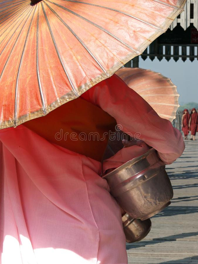 Nun with pink robe and umbrella. Walking on the U bain bridge at Mandalay,Myanmar stock photo