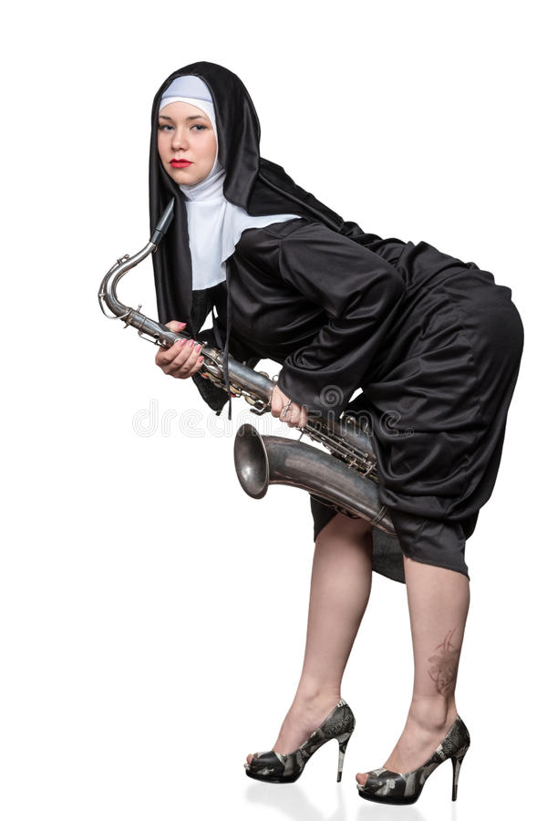 Nun with a saxophone. Portrait of a nun with bright makeup holding a saxophone between legs on white background stock photography