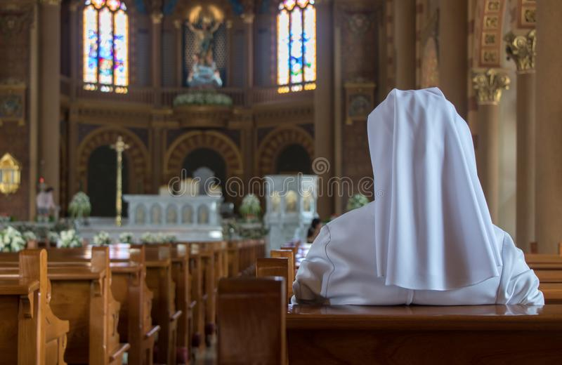 The nun sits in the church stock photo