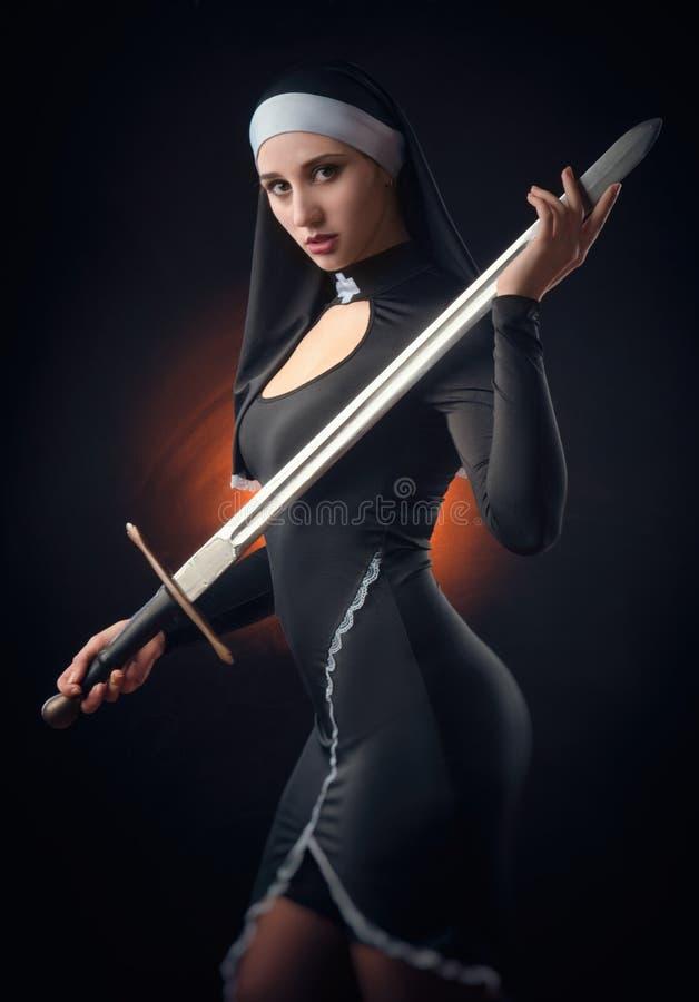 A nun with a weapon in the name of faith royalty free stock photos