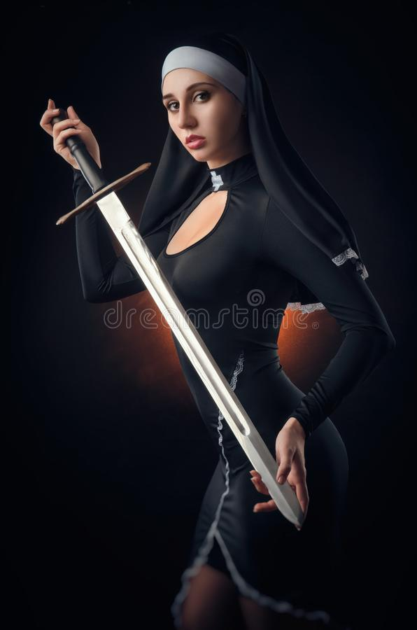 A nun with a weapon in the name of faith stock photo