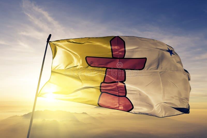 Nunavut landskap av tyg för torkduk för Kanada flaggatextil som vinkar på den bästa soluppgångmistdimman stock illustrationer
