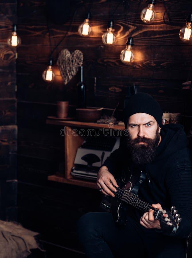 Nunca pare el rock-and-roll Guitarrista de la roca que juega música Hombre barbudo tocar la guitarra Hombre del estilo de la roca foto de archivo