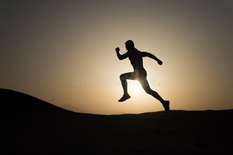 Nunca pare Siluetee el movimiento del hombre que corre delante de fondo del cielo de la puesta del sol El éxito futuro ahora depe imagen de archivo libre de regalías