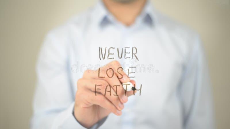 Nunca pierda la fe, escritura del hombre en la pantalla transparente imagen de archivo
